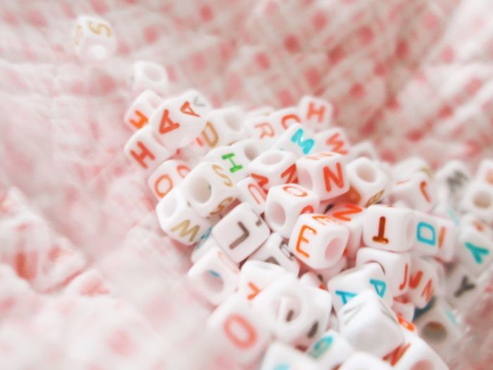 Close-Up Of Toy Blocks With Colorful Alphabets On Fabric