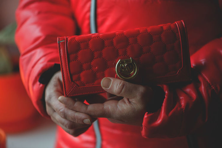 Cropped image of woman holding red purse