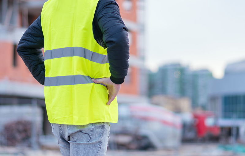 Midsection of worker standing at construction site