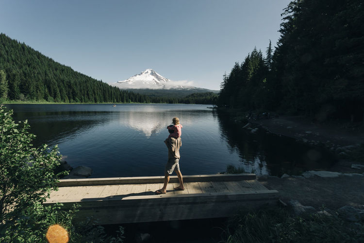 Man standing on lake against sky