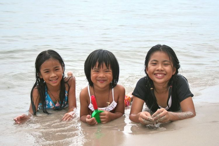 Portrait of happy girls enjoying in water at beach