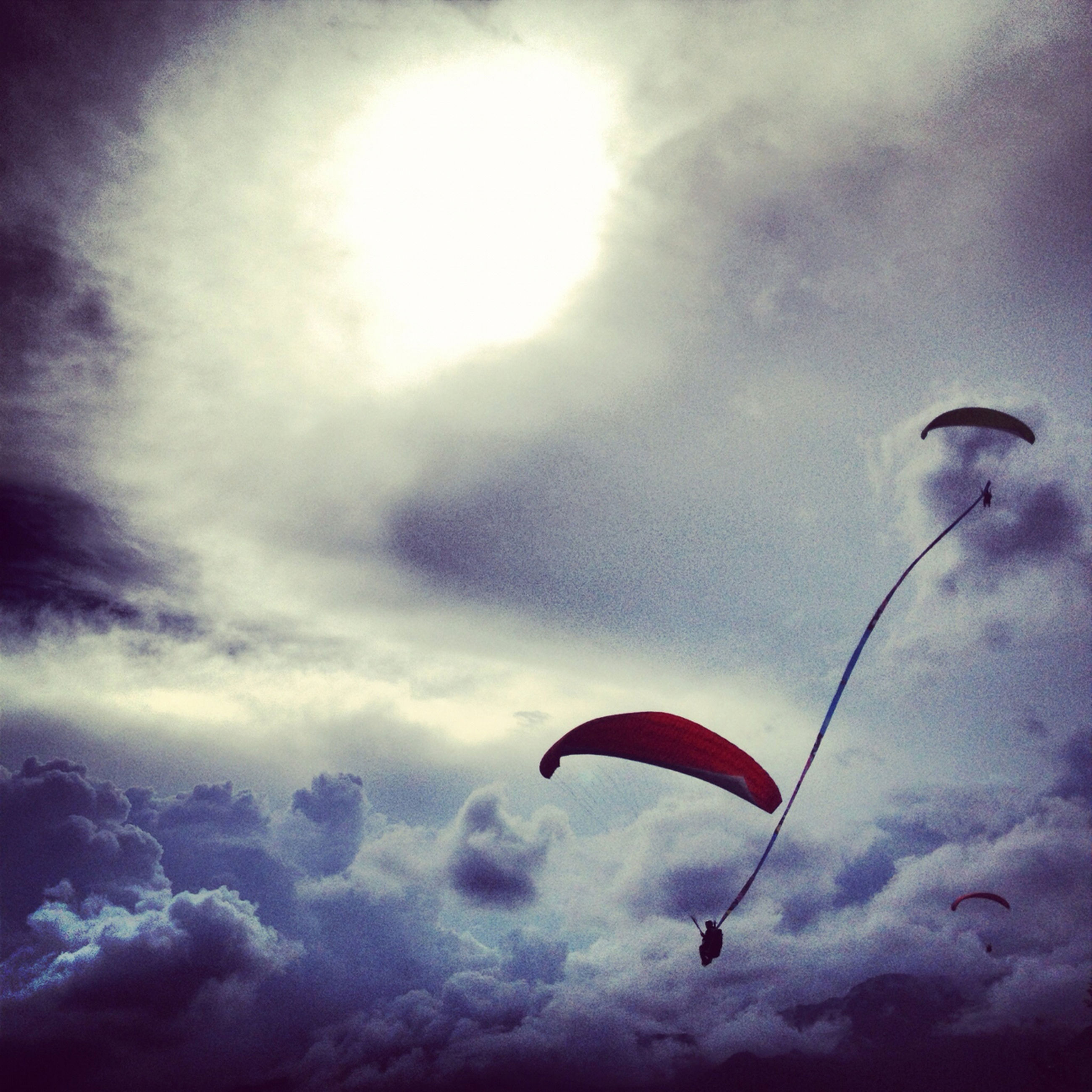 low angle view, sky, cloud - sky, mid-air, flying, cloudy, cloud, nature, beauty in nature, tranquility, scenics, outdoors, parachute, adventure, weather, freedom, day, paragliding, no people, tranquil scene