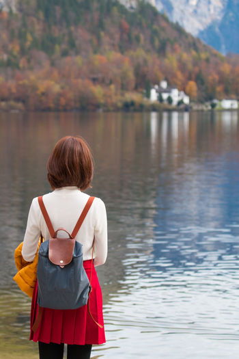 Rear view of woman standing in lake
