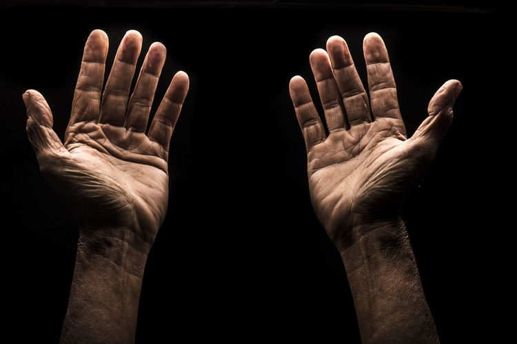 Person gesturing hands against black background