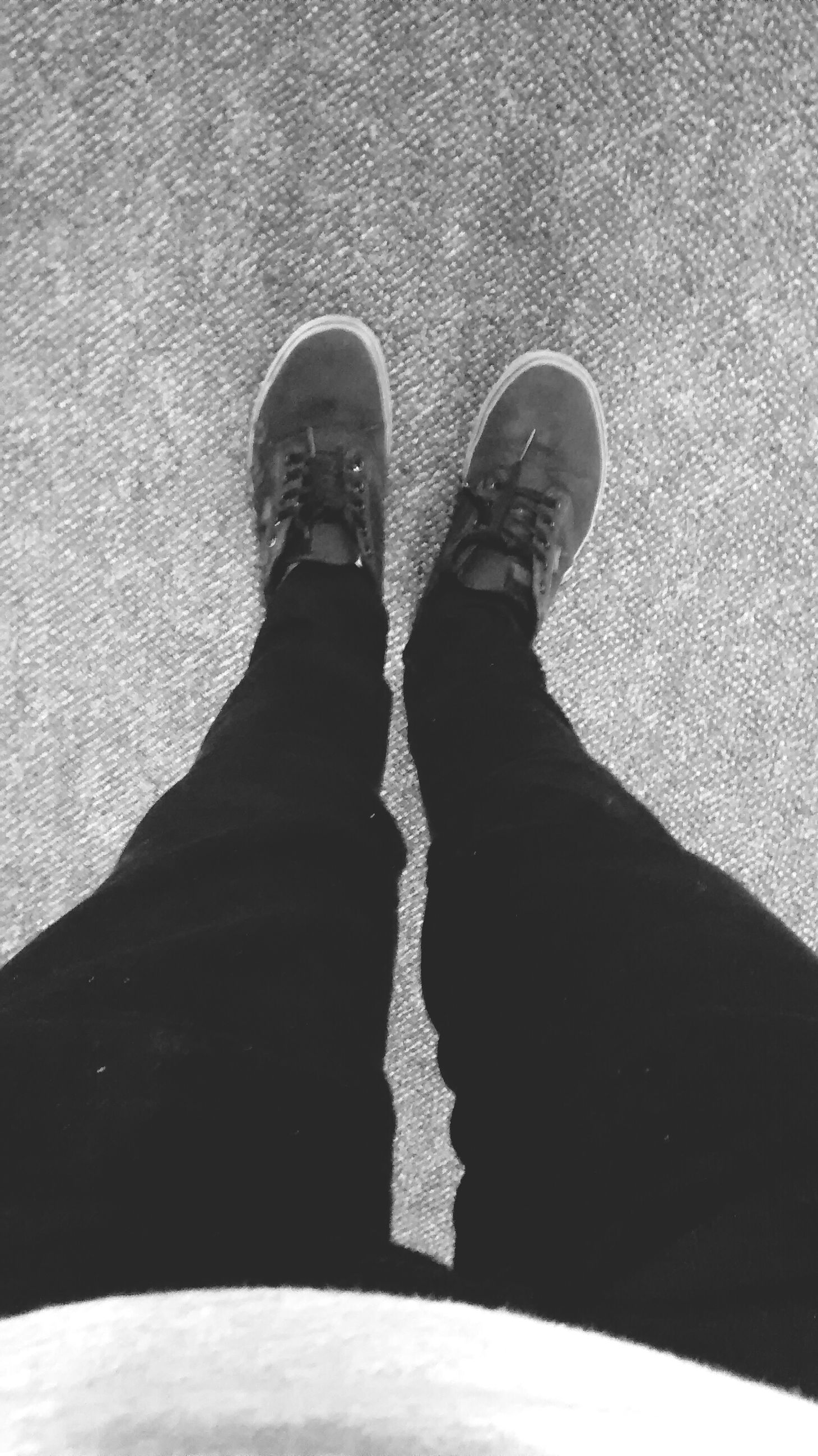 low section, shoe, person, high angle view, street, standing, shadow, personal perspective, lifestyles, footwear, sunlight, men, outdoors, day, leisure activity, road, unrecognizable person, footpath