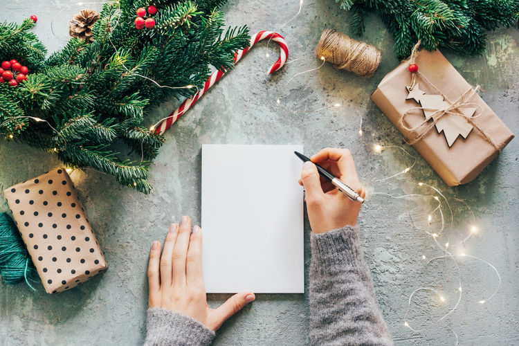 Cropped image of woman hand writing on notebook with christmas ornaments