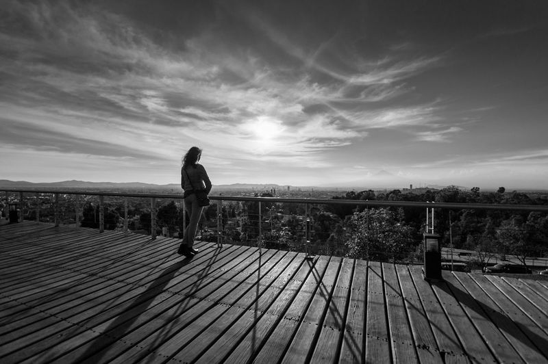 Rear View Of Woman Standing By Railing Against Cloudy Sky