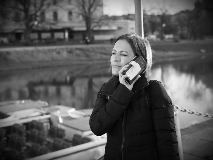 Woman Talking On Mobile Phone Against Lake