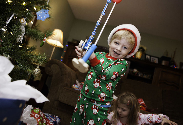 Boy Playing With Toy Fishing Rod At Home During Christmas