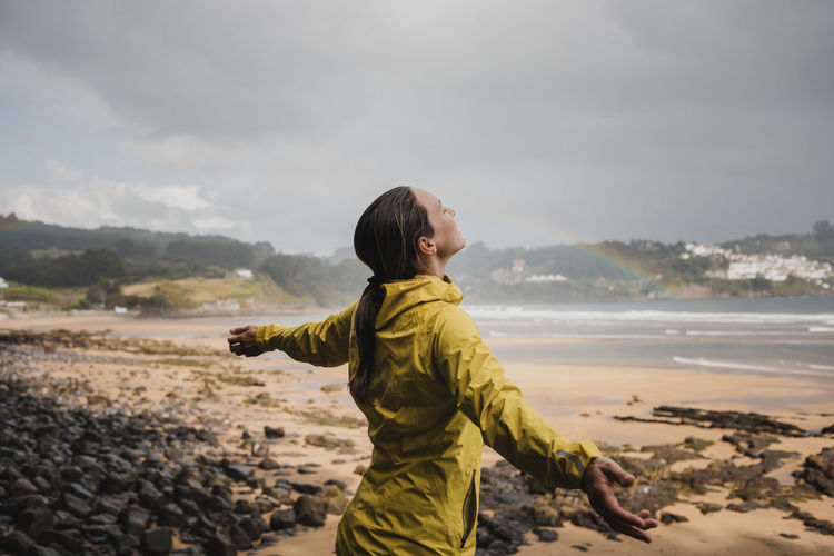 Side view of boy standing on beach