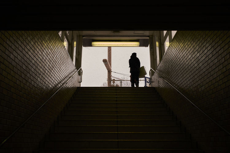 Low angle view of silhouette woman standing on staircase