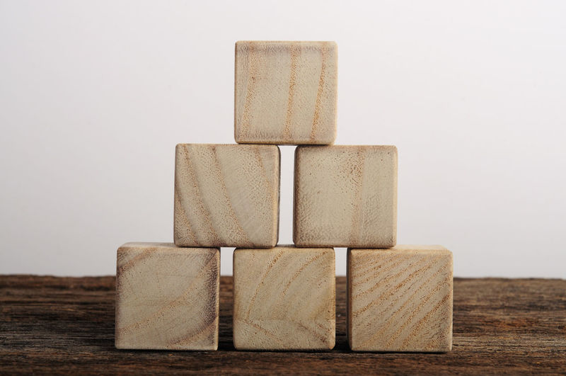 Close-up of wooden blocks against white background on table