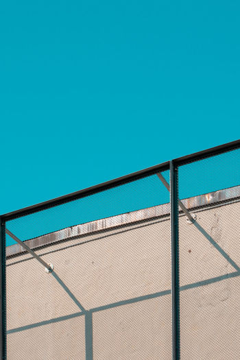 Low angle view of railing against clear blue sky