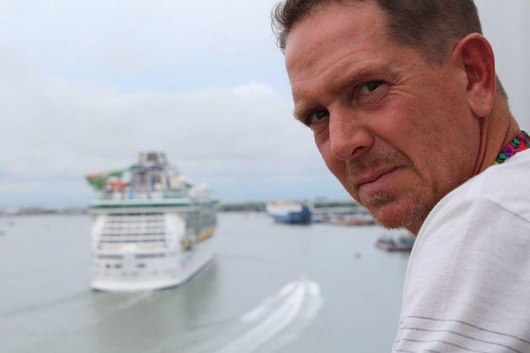 Close-up portrait of man against sea