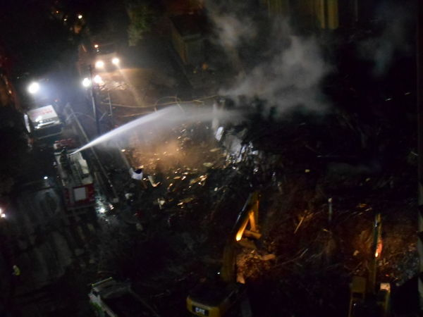 Day 2, Evening. Building Collapse: Inner City Calamity in downtown São Paulo at Largo do Paissandú; 3 am May 1, 2018. The abandoned former Federal Police steel and glass skyscraper, which had been invaded by street people, imploded in the early morning hours and the neighboring buildings, including the Lutheran Church on Avenida Rio Branco, were destroyed by fire as well. This photo taken in the evening of May 2, 2018 at Largo do Paissandú. It shows the round-the-clock efforts by firefighters and the debris removal crew. Current Events Largo Do Paissandu May 1, 2018 May 2, 2018 Night Photography Susan A. Case Sabir Unretouched Photography Building Collapse Building Fire Building Implosion Burning Building Controlled Chaos Dangerous Situation Debris Removal Downtown São Paulo Firefighters In Action Heat - Temperature High Angle View Implosion Responsiveness Smoke - Physical Structure Unexpected Event Urban Photography Urban Strife Work-in-progress