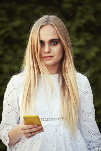 Portrait of beautiful young woman using smart phone outdoors