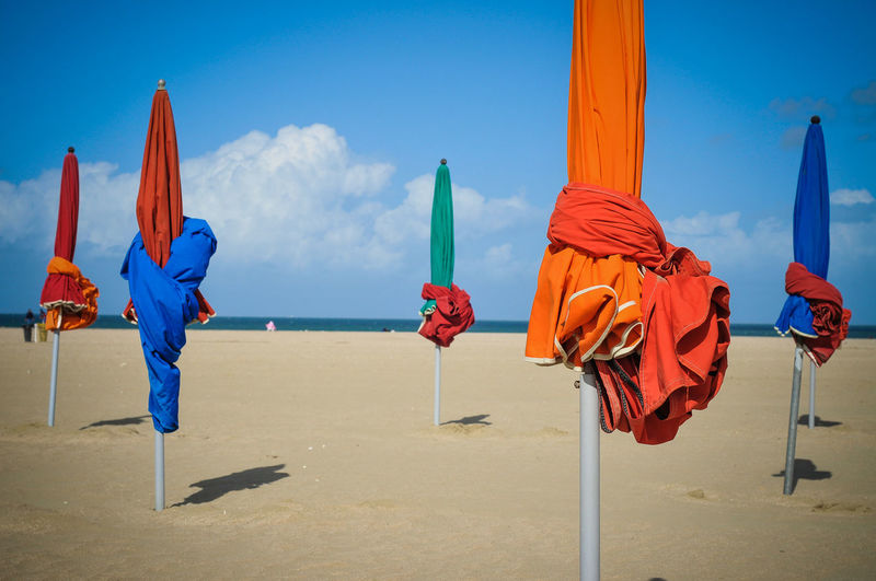 Colorful Closed Parasols Against Sky At Sandy Beach On Sunny Day