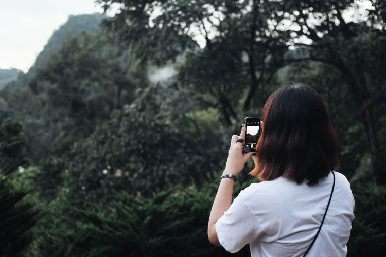 young woman standing and taking photo by smartphone Beauty In Nature Cellphone Photography Girl Phone Selfie Smartphonephotography Standing Take Photos White Shirt Woman