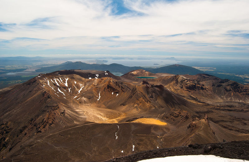 High angle view of volcanic landscape against cloudy sky