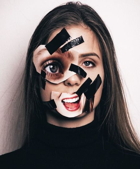 Close-up portrait of sad young woman with adhesive tape and photographs against wall