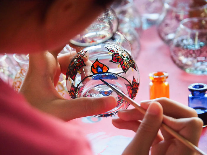 The girl is using a paintbrush painted on  glass.concept  kids's  training .