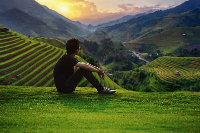 Man sitting on field against mountains