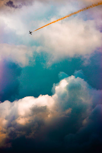 Flying Airplane Air Vehicle Vapor Trail Cloud - Sky Mid-air Airshow Smoke - Physical Structure Sky Outdoors No People Water Multi Colored Nature Military Airplane Day Aerobatics Fighter Plane Tranquil Scene Backgrounds Full Length Adventure Sunlight Nature Cloudy