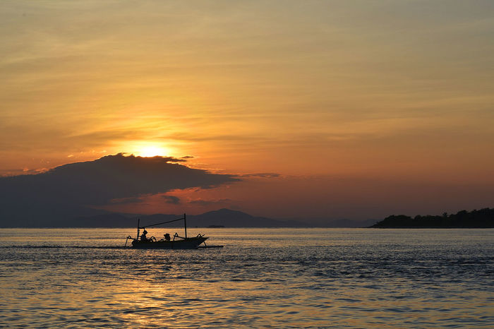 It is time to go home Beauty In Nature Boat Cloud Cloud - Sky Idyllic Mode Of Transport Mountain Nature Nautical Vessel Non-urban Scene Orange Color Outdoors Remote Rippled Sailing Scenics Sea Sky Sun Sunrise Tourism Tranquil Scene Tranquility Water Waterfront