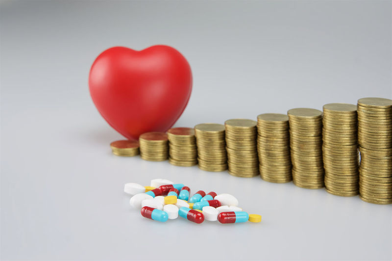 Close-up of coins by pills and heart shape stress ball on white background