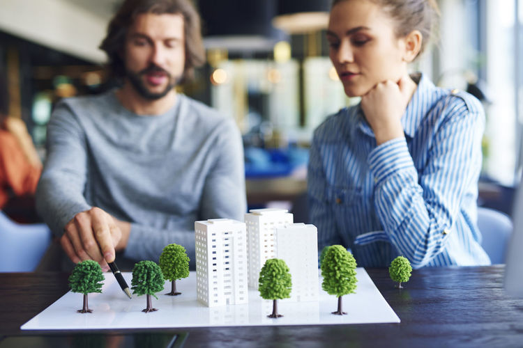 Business people discussing over architectural model