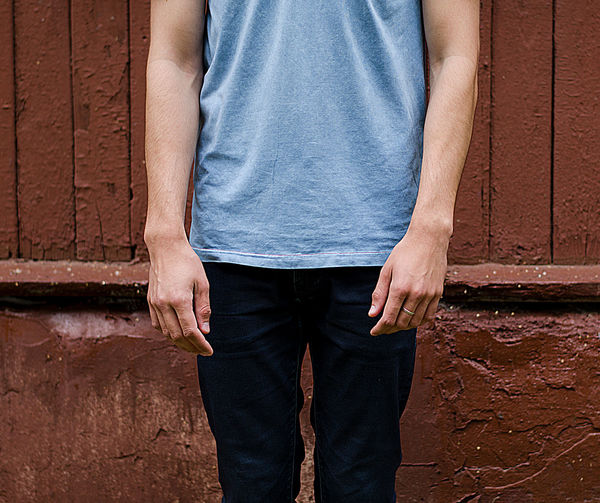 Midsection of man standing against wall