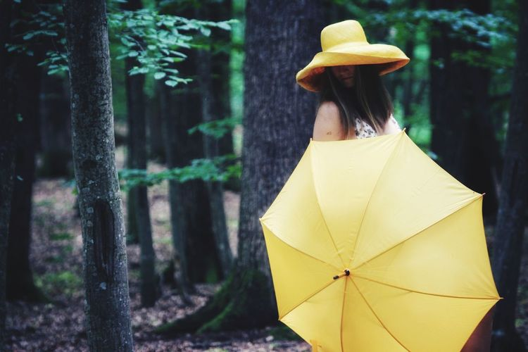 Woman holding umbrella while standing in forest