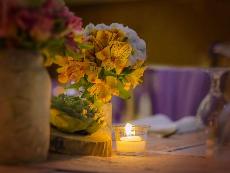 Rustic country style dining Bouquet Candle Candlelight Close-up Devotion Dining Dinner Firelight Flower Flower Arrangement Flower Head Focus On Foreground Fragility Freshness Glow Guidance Horizontal Indoors  Light Nature No People Orange Table Yellow
