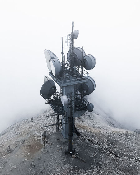 High angle view of telecommunications tower on mountain during foggy weather