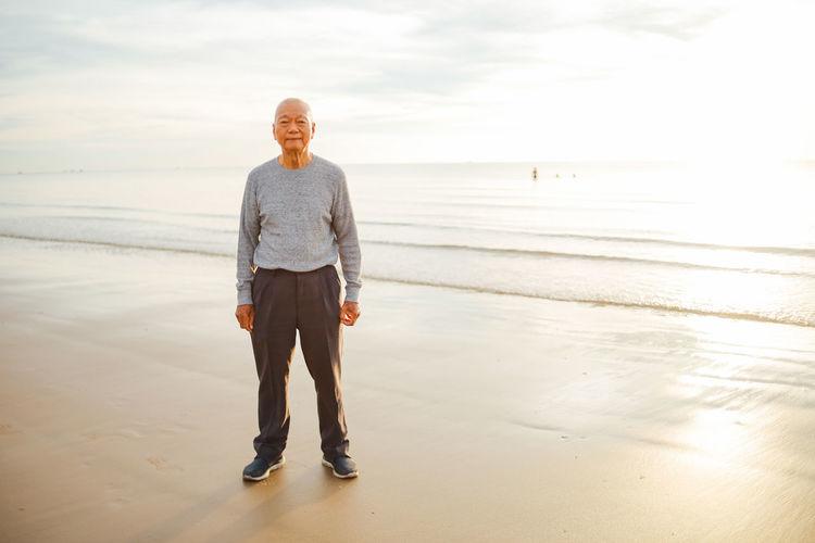 Portrait of senior man standing at beach against sky during sunset