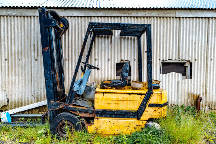 Abandoned forklift by barn