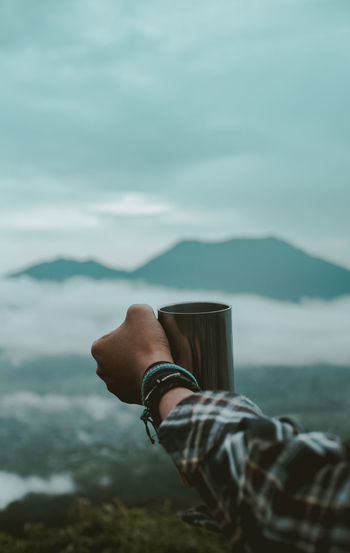 Hand Of Hiker Holding Mug Against Sky