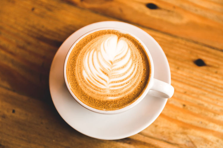 EyeEmNewHere Cappuccino Close-up Coffee - Drink Coffee Cup Day Drink Food And Drink Freshness Froth Art Frothy Drink High Angle View Latte Leaf No People Refreshment Saucer Table Warm Warm Up Wood - Material