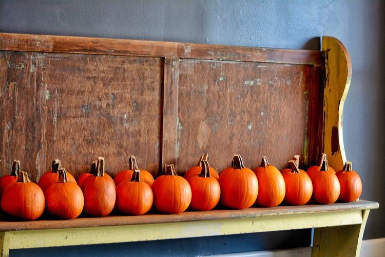Close-Up Of Pumpkins Arranged In Row On Wood