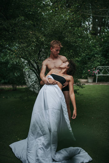 Young couple sitting on grass against trees