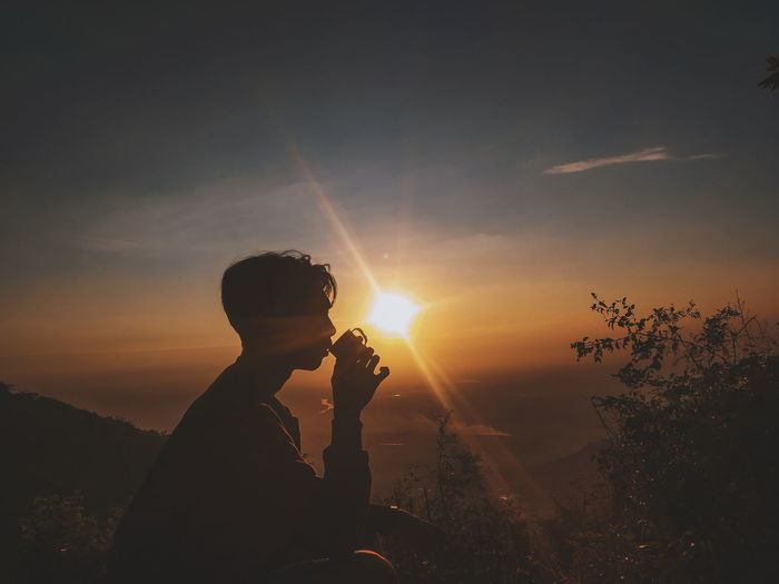 Silhouette man drinking coffee against sky during sunset