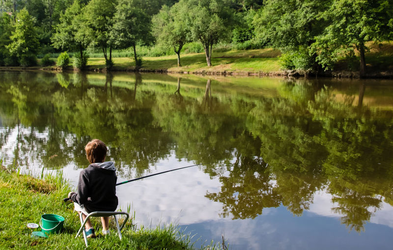 Boy fishing in lake against trees