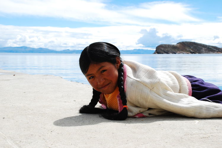 Portrait Of Mid Adult Woman Lying On Sand At Beach Against Cloudy Sky