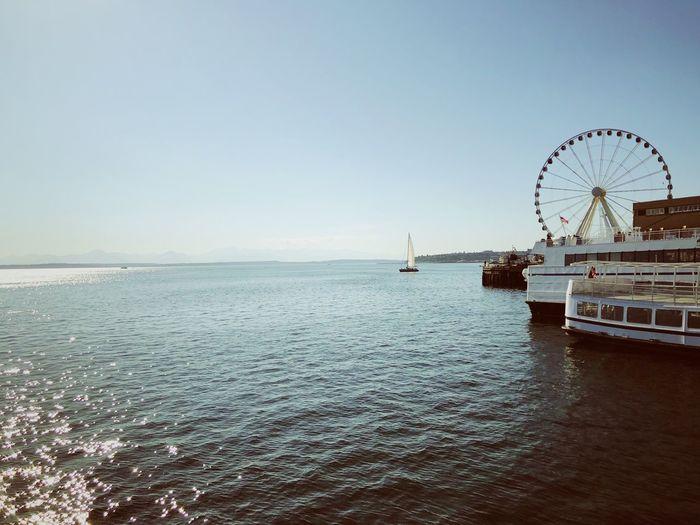 Ferris wheel by sea against clear sky