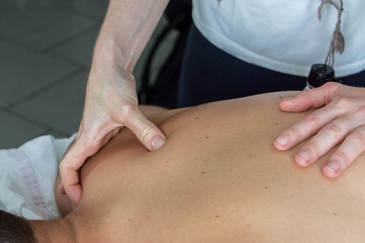 Midsection Of Physical Therapist Giving Massage To Patient