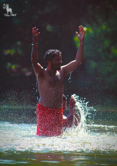 Full length of shirtless man splashing water