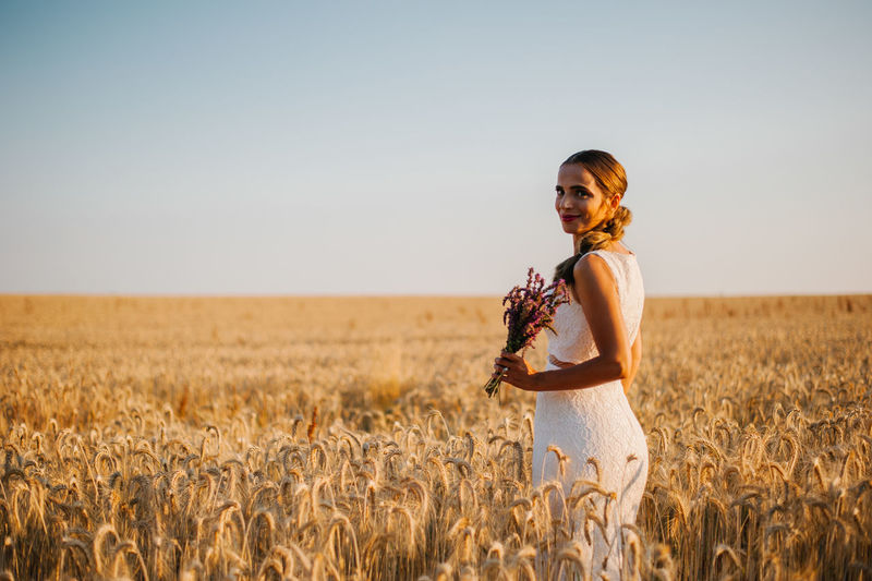 Portrait of bride standing by landscape against clear sky