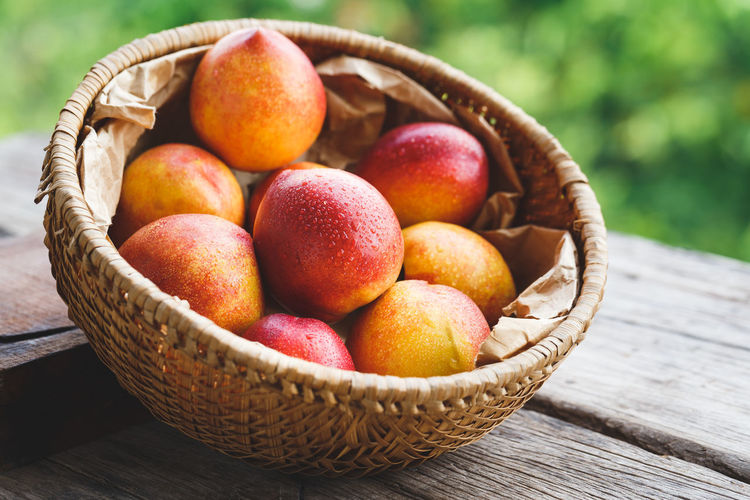 High angle close-up of wet peaches in basket on wooden table