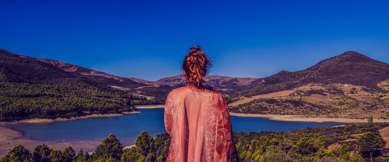 Rear view of woman standing on mountain against clear blue sky
