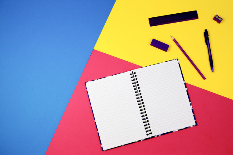 High angle view of spiral notebook with school supplies on colored background